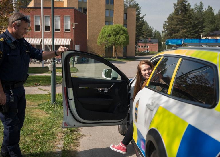 Bild på deltagare som kliver ur en polisbil