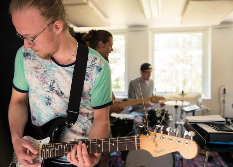 Bild på deltagare som spelar gitarr i en ensemble