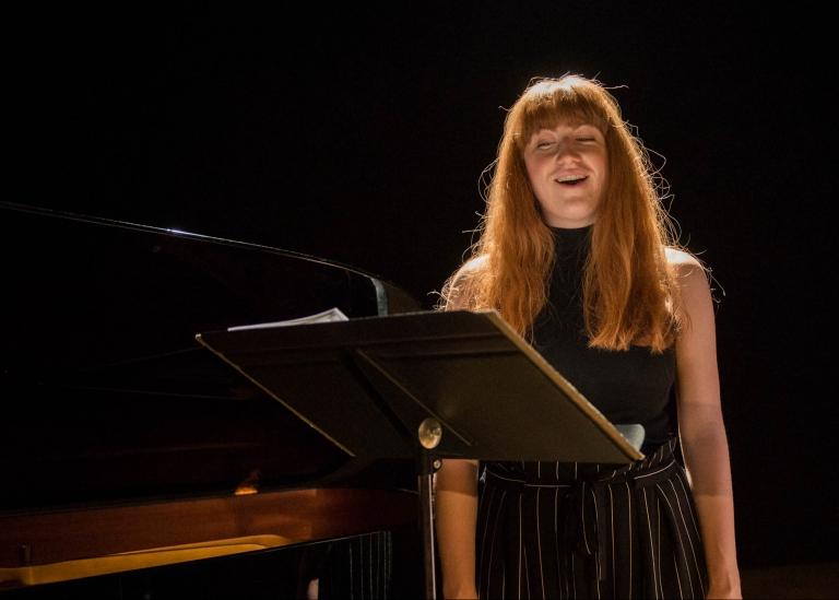 Bild på deltagare som sjunger på en scen
