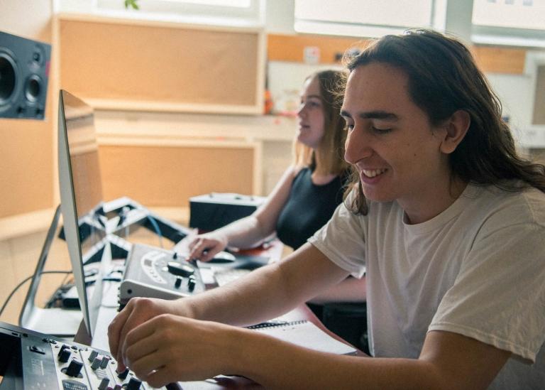 Bild på deltagare som sitter vid en dator i en studio