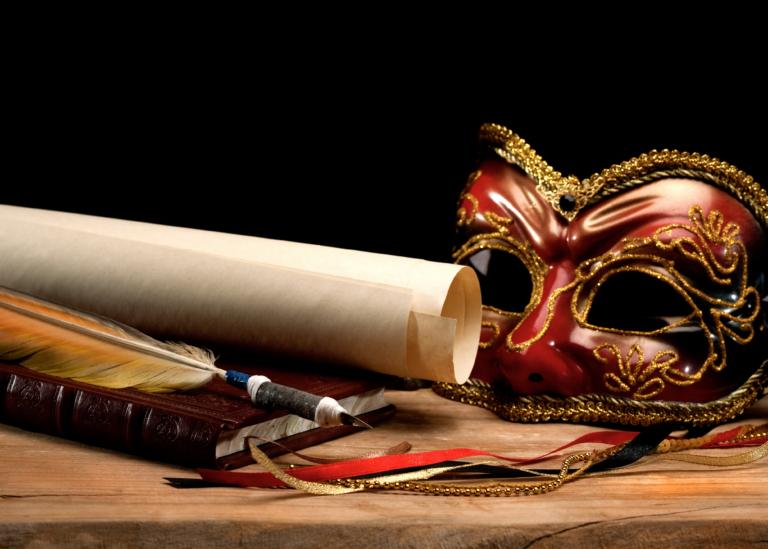 Bild på penna, manuskript och en teatermask